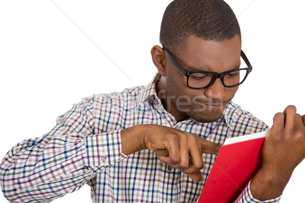 Man, squinting eyes pointing at a page inside book Stock photo © ichiosea