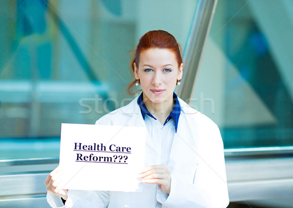 Confused doctor holding health care reform???sign Stock photo © ichiosea