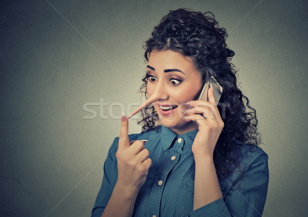 Concept of customer support liar with long nose. Woman talking on mobile phone telling lies  Stock photo © ichiosea