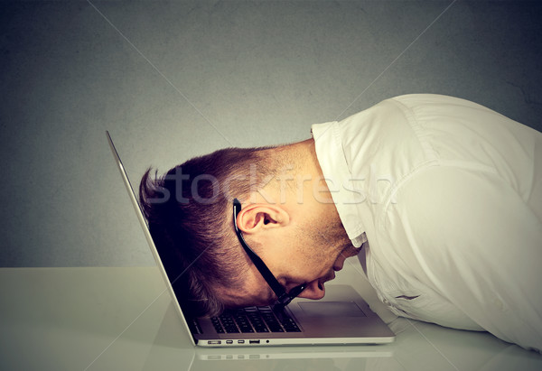 Desperate employee stressed young man resting head on laptop keyboard  Stock photo © ichiosea