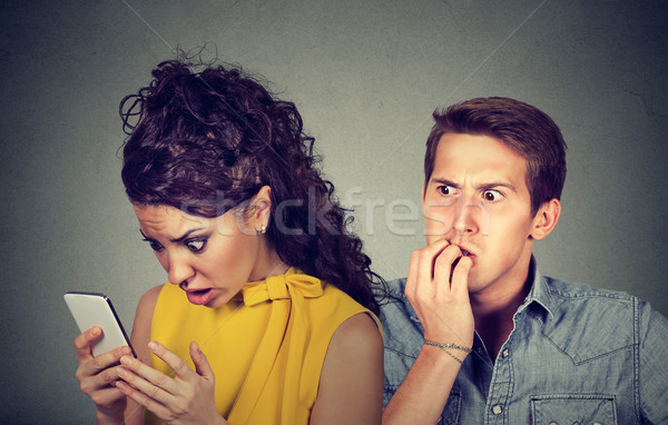 Cheating boyfriend. Man nervously biting fingernails while shocked girlfriend reading text messages  Stock photo © ichiosea