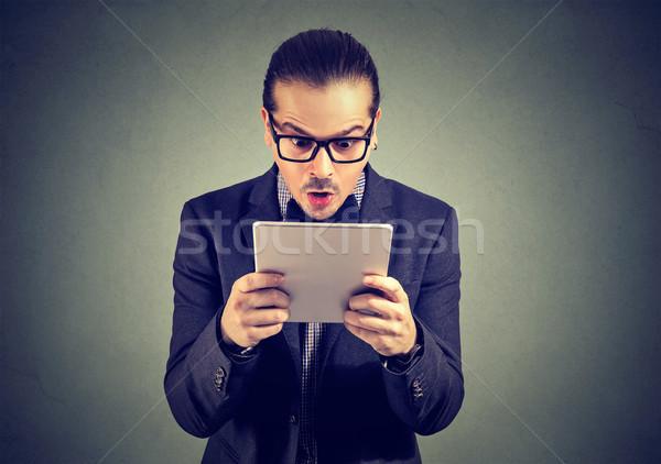 Shocked man staring at tablet Stock photo © ichiosea