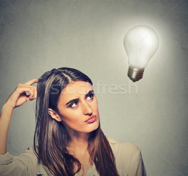 beautiful girl woman thinks looking up at bright light bulb Stock photo © ichiosea