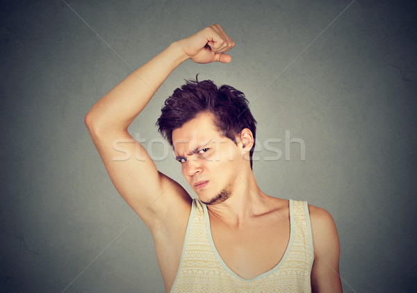 man, smelling, sniffing his armpit, something stinks bad, foul odor  Stock photo © ichiosea