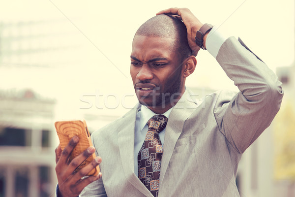 stressed man holding cellphone looking at screen with cross face expression  Stock photo © ichiosea