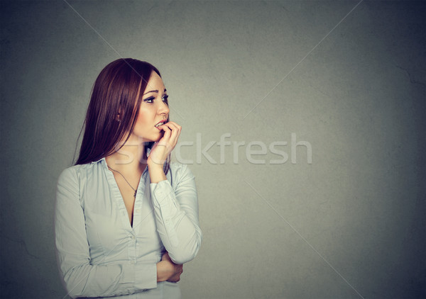 Preoccupied anxious young woman biting fingernails  Stock photo © ichiosea