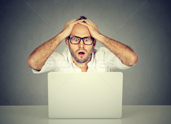 Shocked young man looking at laptop computer anxious with open mouth Stock photo © ichiosea