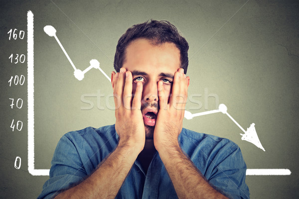 frustrated stressed young man desperate with financial market chart graphic going down Stock photo © ichiosea