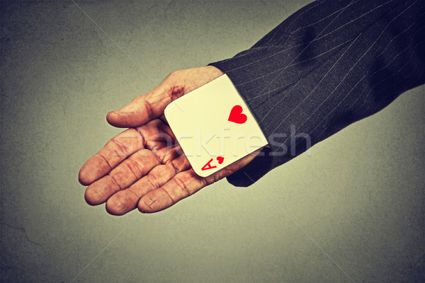Stock photo: cropped image senior man hand pulling out a hidden ace from the sleeve