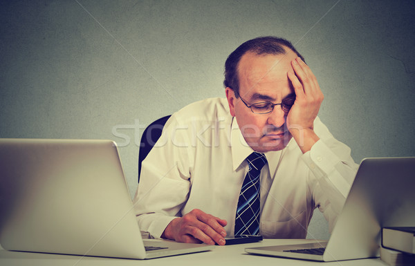 tired sleepy middle aged man sitting at desk with books in front of two laptop computers Stock photo © ichiosea