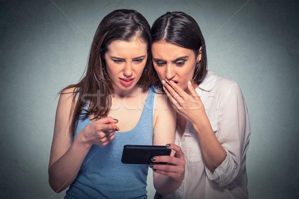 Kettő elégedetlen nők néz mobiltelefon arc Stock fotó © ichiosea