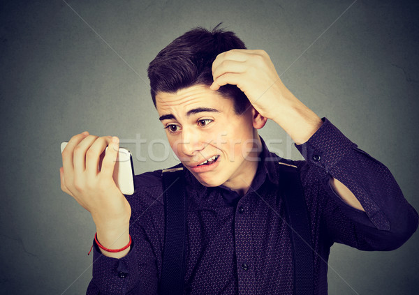 Preoccupied upset man surprised he is losing hair receding hairline  Stock photo © ichiosea