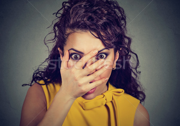 Scared woman covering her face with hands peeking through fingers  Stock photo © ichiosea