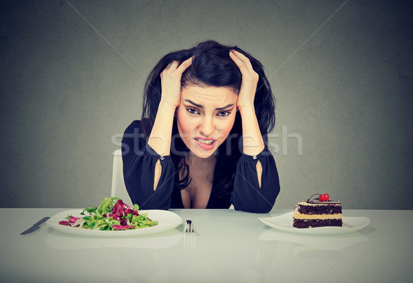 Woman tired of diet restrictions deciding to eat healthy food or cake she is craving  Stock photo © ichiosea