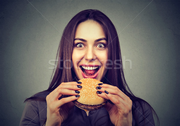 Fast food is my favorite. Woman eating a hamburger enjoying the taste  Stock photo © ichiosea