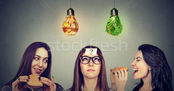 Two women eating hamburgers looking at thoughtful girl with question mark  Stock photo © ichiosea