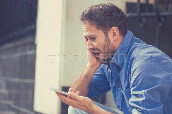 Desperate sad young man looking at bad text message on his mobile phone Stock photo © ichiosea