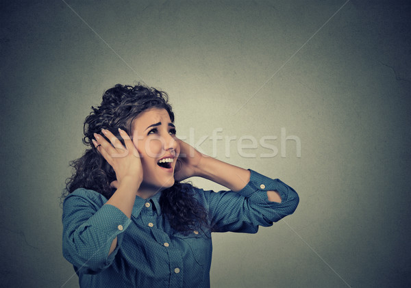 unhappy stressed woman covering her ears looking up stop making loud noise  Stock photo © ichiosea