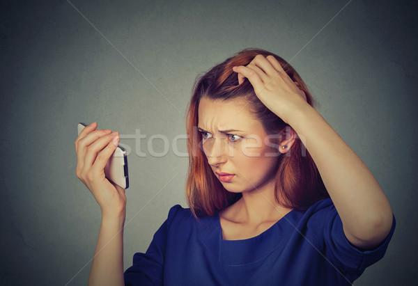 unhappy frustrated upset woman surprised she is losing hair, receding hairline Stock photo © ichiosea