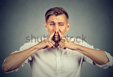 Woman pinches nose with fingers hands looks with disgust something stinks bad smell  Stock photo © ichiosea
