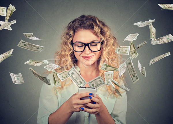 woman using smartphone with dollar bills flying away from screen  Stock photo © ichiosea