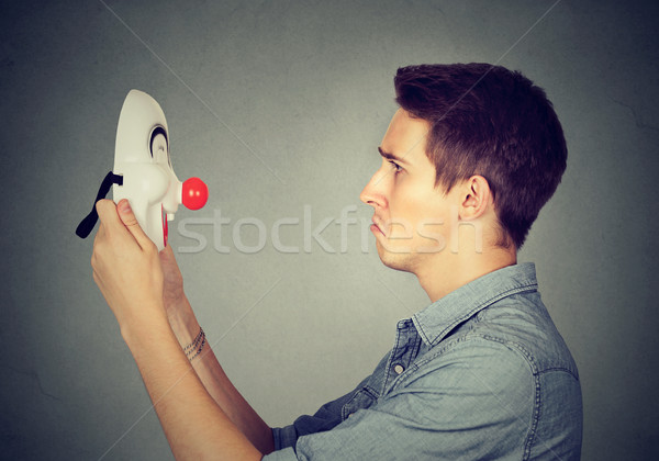 sad man holding looking at happy clown mask   Stock photo © ichiosea