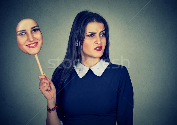 woman with disgusted expression holding mask expressing cheerfulness Stock photo © ichiosea