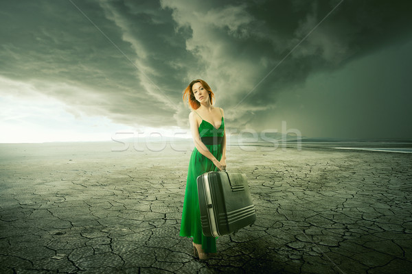 Woman in green dress with suitcase standing alone in the middle of the desert Stock photo © ichiosea