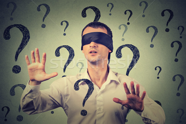 blindfolded man stretching his arms out walking through many question marks  Stock photo © ichiosea