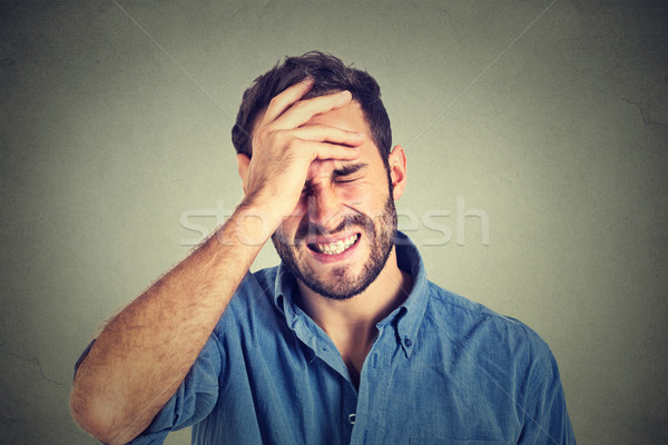 Portrait stressed man suffering from headache isolated on gray wall background Stock photo © ichiosea
