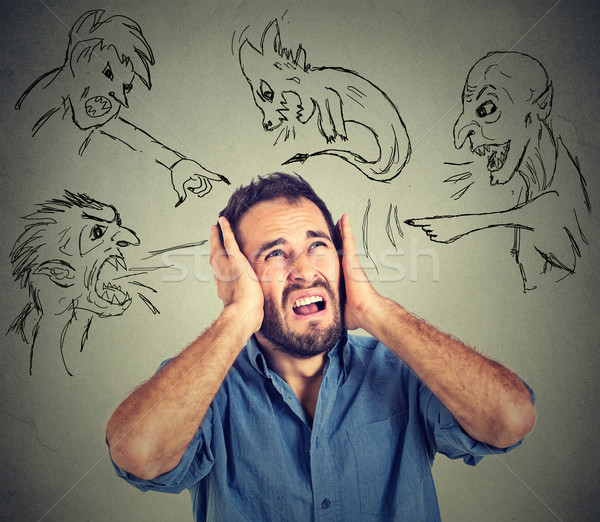 Stressed young man covers his ears with his hands evil guys pointing fingers at him Stock photo © ichiosea