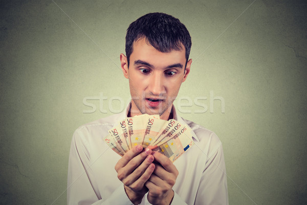 Young greedy business man counting money Stock photo © ichiosea