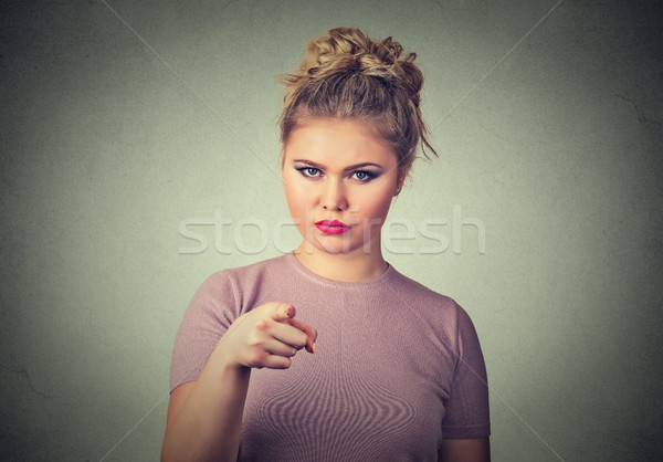 angry young woman pointing at camera isolated on grey wall background Stock photo © ichiosea