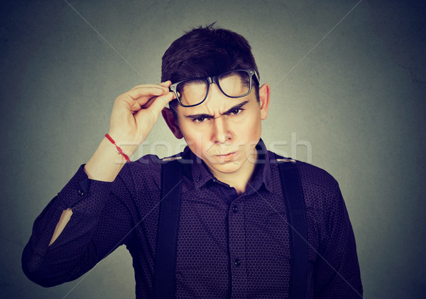 Stock photo: Hard to please young man skeptically looking at camera