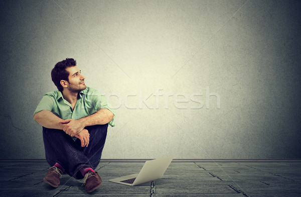 man with laptop computer sitting on a floor planning daydreaming   Stock photo © ichiosea