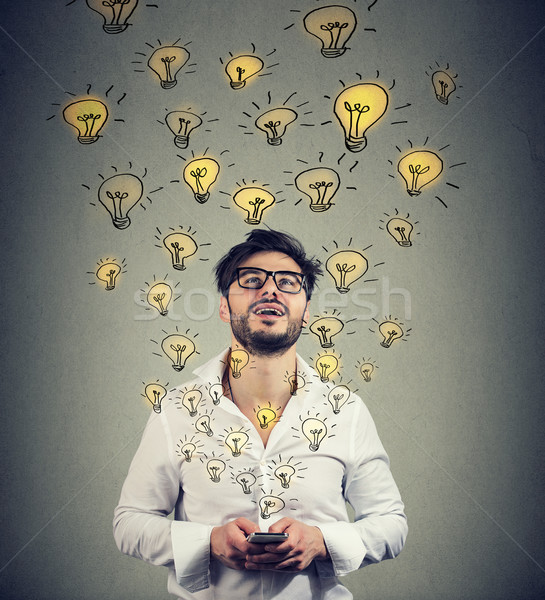 man in eyeglasses with smarpthone producing plenty of successful ideas.  Stock photo © ichiosea