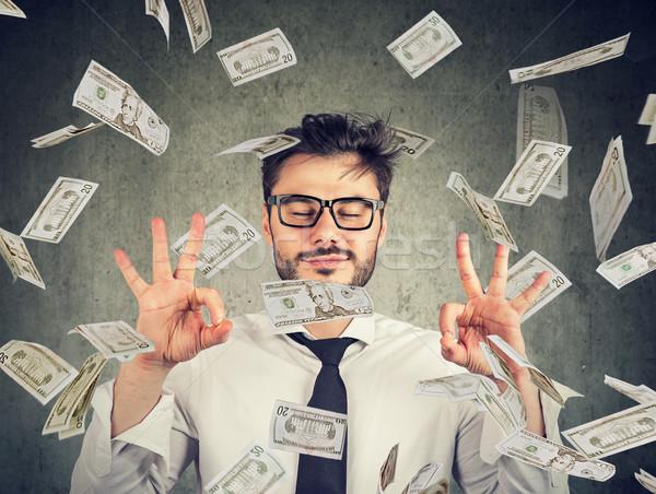 Business man meditating under money rain Stock photo © ichiosea