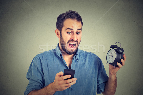 surprised business man with alarm clock looking at smart phone Stock photo © ichiosea