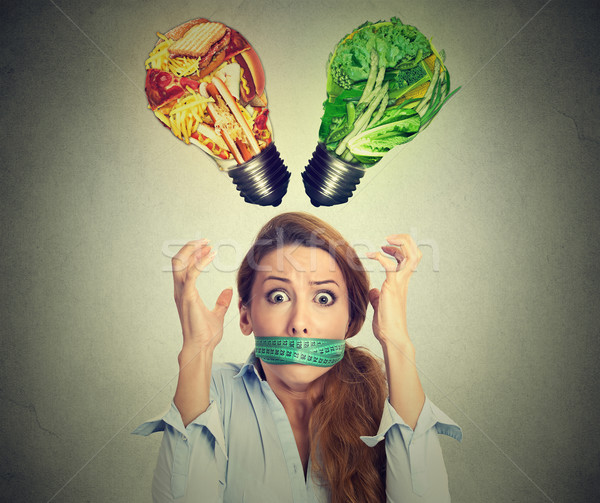 Diet restriction stress concept. Frustrated woman with measuring tape around mouth  Stock photo © ichiosea