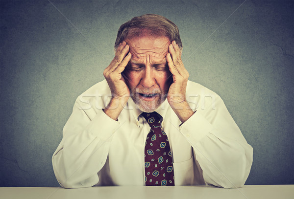 Stressed hopeless elderly business man in depression sitting at the office table  Stock photo © ichiosea
