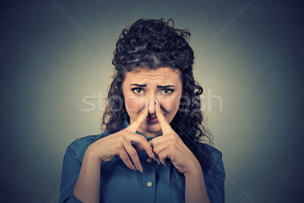 woman pinches nose with fingers looks with disgust something stinks bad smell Stock photo © ichiosea