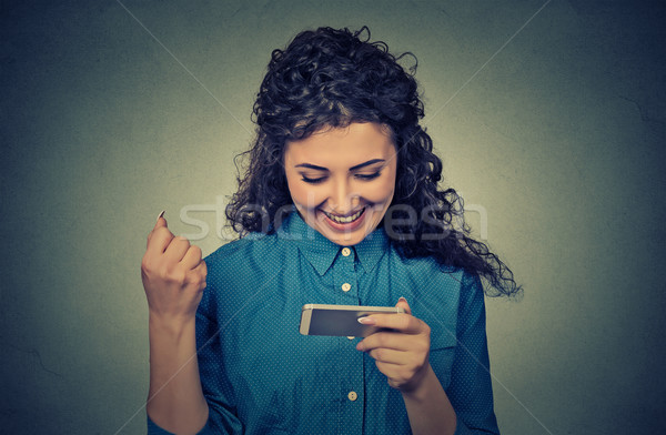 young woman looking at her mobile phone and smiling pumping fist celebrates success Stock photo © ichiosea