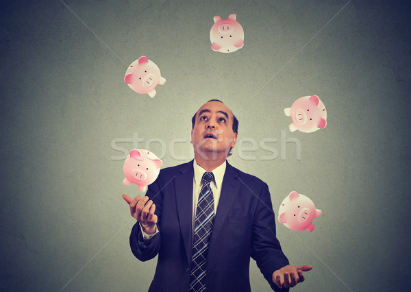 Middle aged business man juggling money piggy bank  Stock photo © ichiosea