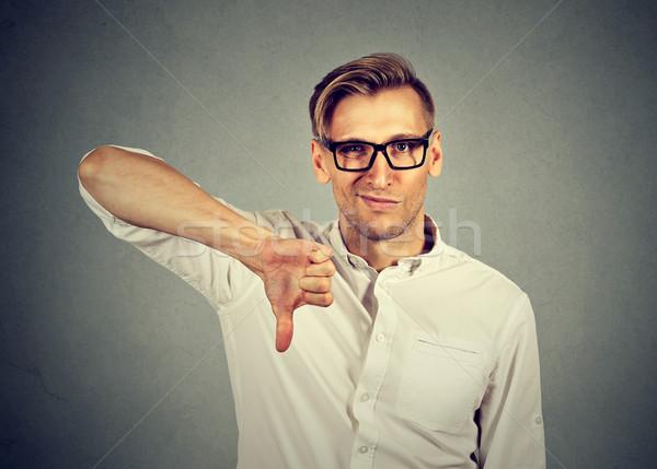 Mérges boldogtalan férfi mutat hüvelykujjak lefelé Stock fotó © ichiosea
