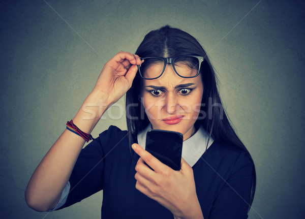 confused woman with glasses having trouble seeing cell phone Stock photo © ichiosea
