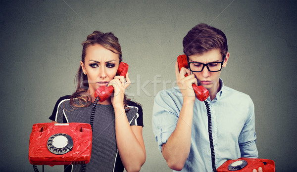 Sad confused young couple man and woman talking to each other over the phone  Stock photo © ichiosea