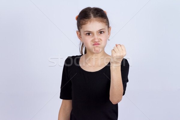 Stock photo: Angry little girl showing fist to someone
