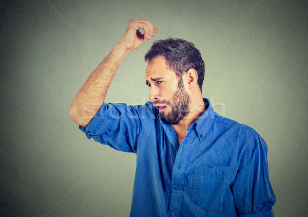 young man, smelling, sniffing his armpit, something stinks, very bad, foul odor Stock photo © ichiosea