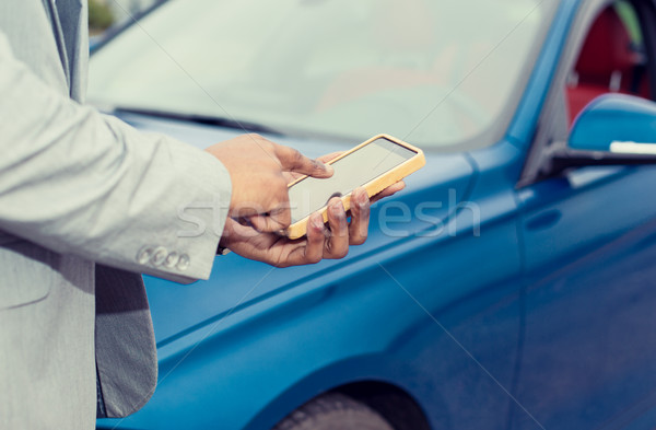 Mobile phone apps for car owners concept. Man using smart phone  Stock photo © ichiosea
