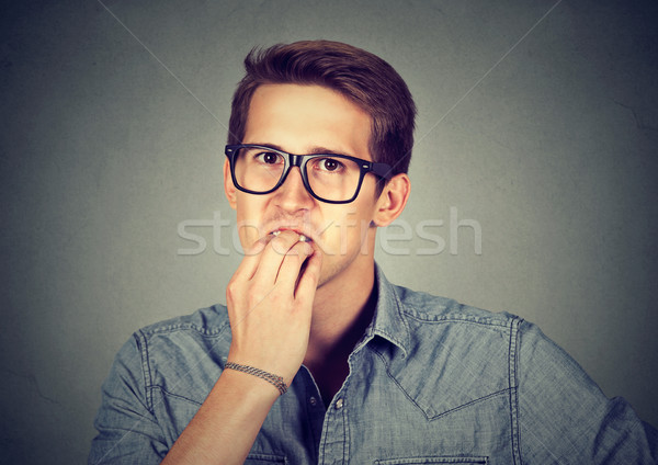 Preoccupied anxious man biting fingernails nervously  Stock photo © ichiosea
